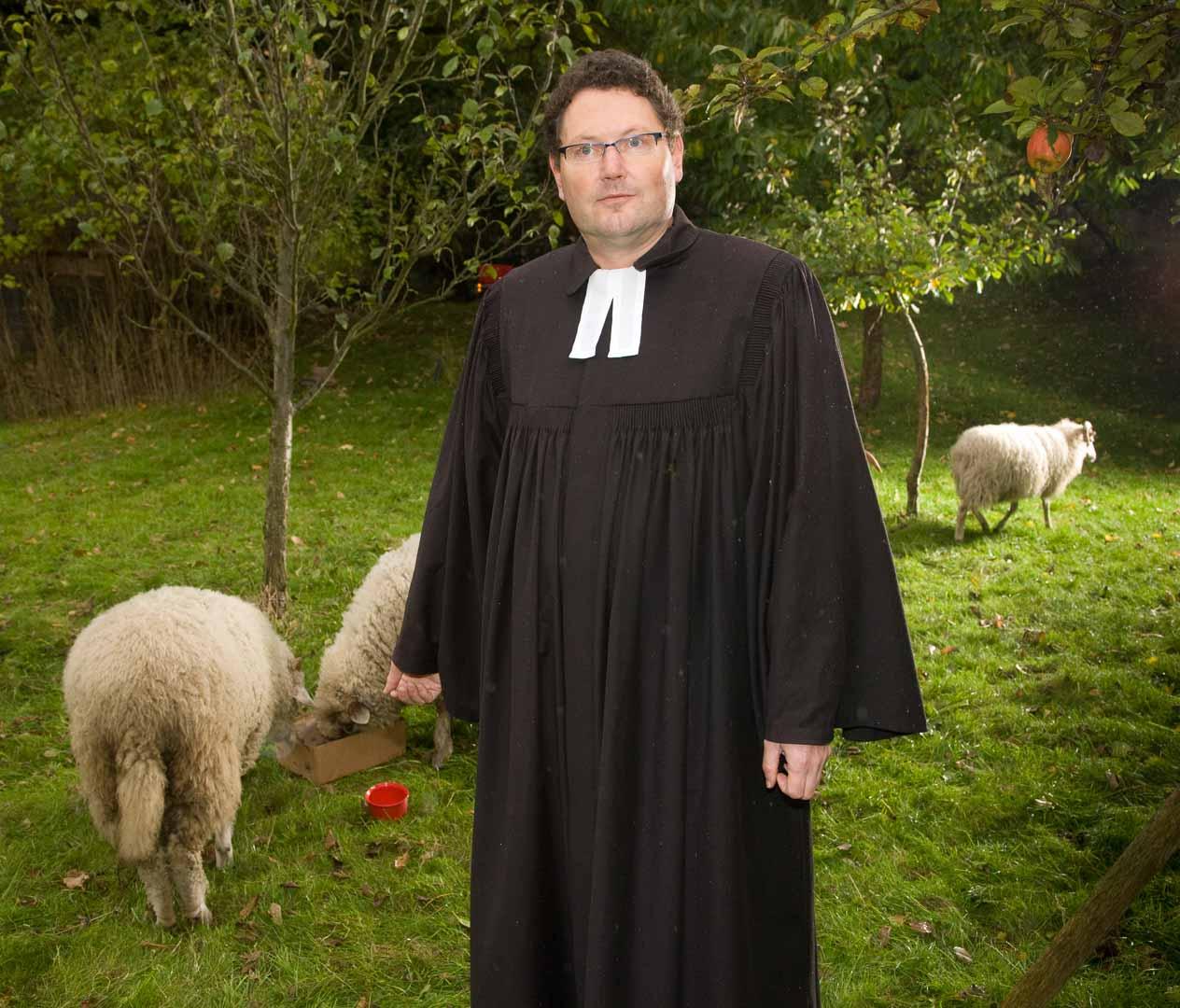 Armin Prä , Pfarrer im Garten des Pfarrhauses Dobin mit seinen Robustschafen.